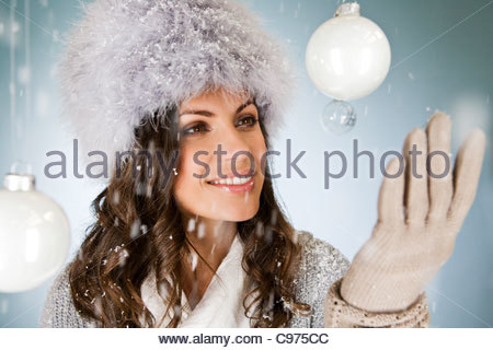 A young woman looking at a glass bauble - Stock Photo