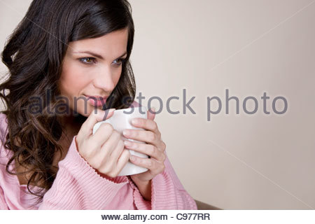 A young woman drinking a cup of hot chocolate - Stock Photo