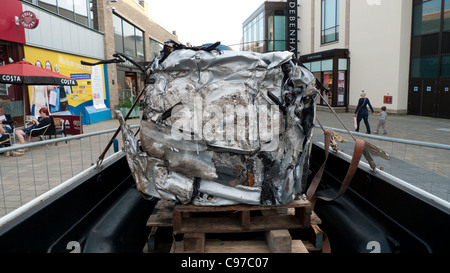 A compressed scrap metal car on the back of a pick-up truck. - Stock Photo