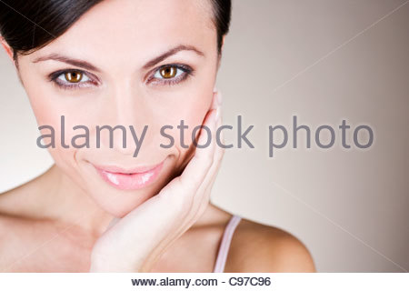Portrait of a young woman touching her face - Stock Photo