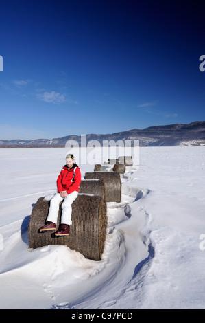 12 years old girl sitting on a hay bale in a field  (Ličko polje) during winter, Gorski kotar, Croatia - Stock Photo