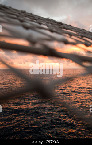 Sunset view through bowsprit net of sailing cruiseship Star Flyer (Star Clippers Cruises) Pacific Ocean near Costa - Stock Photo