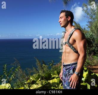 Hiker on the Kalalau Trail on Kauai gazes at ocean - Stock Photo