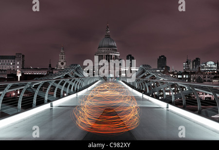 Light Art view of Millennium Bridge crossing the River Thames and St. Paul's Cathedral at night, London, England, - Stock Photo