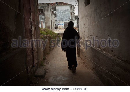 A local woman wearing a head shawl walking down an alleyway in Stonetown - Stock Photo