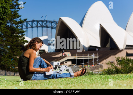A backpacker writes postcards with Sydney Opera House in background.  Sydney, New South Wales, Australia - Stock Photo