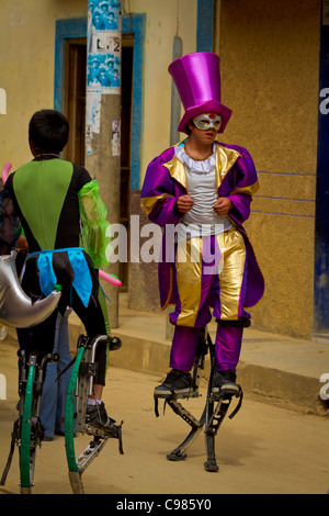 Acrobats on bouncing stilts entertain the crowds in a street parade in Celendin, Peru. - Stock Photo