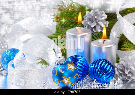 Blue Christmas balls with silver candles over bright background - Stock Photo