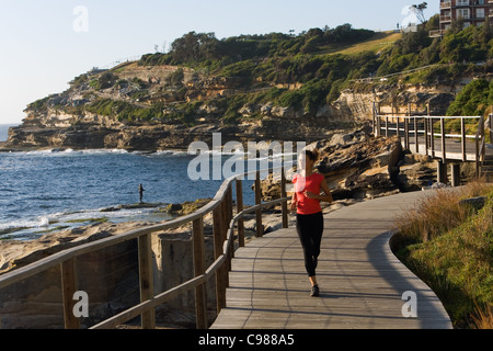 Woman jogging along the Bondi to Coogee coastal path. Sydney, New South Wales, Australia - Stock Photo
