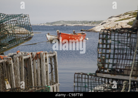 Two fishing boats float in the harbour at Peggy's Cove, Nova Scotia, rocky coast in the distance, lobster cages - Stock Photo