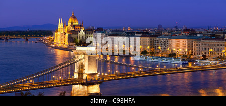 Budapest, Chain Bridge over Danube River and Hungarian Parliament Building at Dusk - Stock Photo
