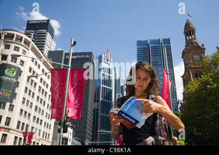 Backpacker reading guidebook with city skyline in background.  Sydney, New South Wales, Australia - Stock Photo