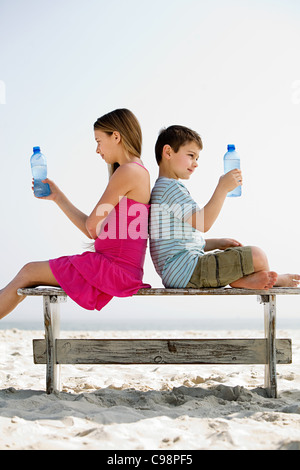 Girl and boy holding bottles water on beach - Stock Photo