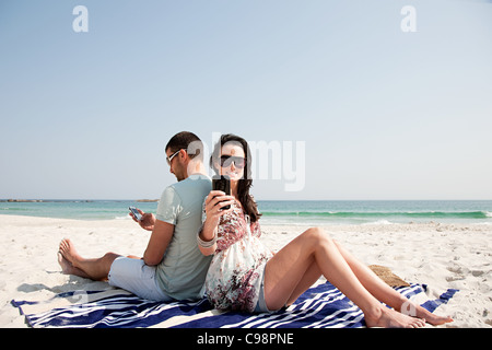 Couple sitting back to back on beach while using mobile phones - Stock Photo