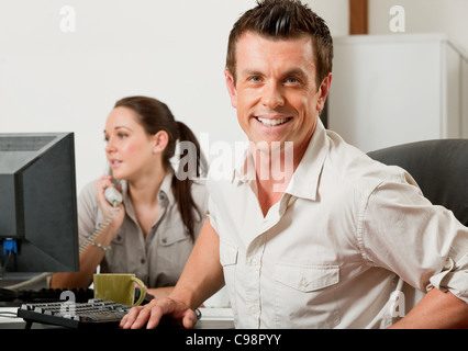 Man getting up from behind his desk - Stock Photo