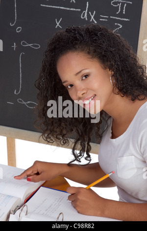 High school or college African-American student by desk math class. Blackboard with advanced mathematical formulas - Stock Photo
