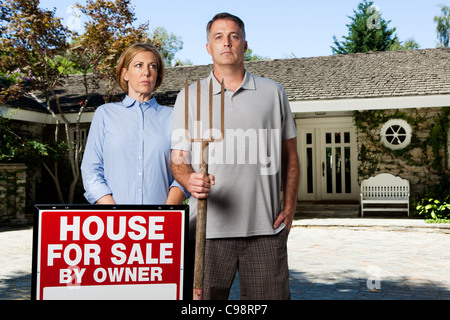 Mature couple standing outside newly bought property style American Gothic - Stock Photo