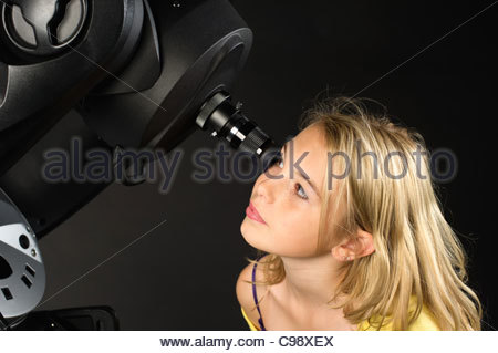 young girl looking at the night sky through an 8 inch reflector telescope - Stock Photo