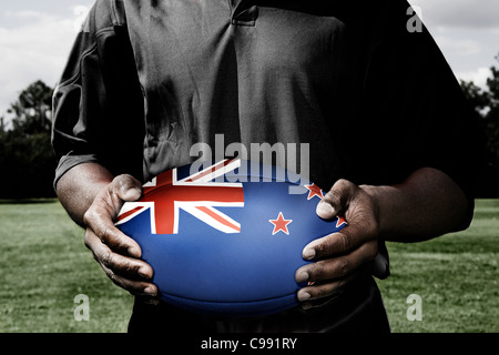 Player holding rugby ball with New Zealand flag - Stock Photo