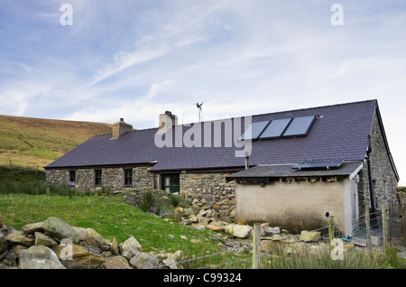 Remote rural cottage with solar panels on roof for heating hot water and generating electricity with small wind - Stock Photo