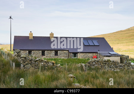 Remote rural cottage with solar panels on roof for heating water and generating electricity with small wind turbine - Stock Photo