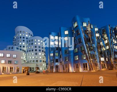 Neuer Zollhof office building at night in modern property development at Media Harbour or Medienhafen in Dusseldorf - Stock Photo