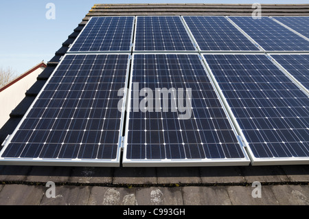 UK, Britain. Solar panels on a house roof with blue sky. - Stock Photo