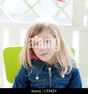 blue eyes kid girl portrait outdoor sit in green chair - Stock Photo