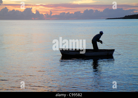 Curaçao Netherlands Antilles Dutch Piscadera Bay Caribbean Sea rowboat man fisherman sunset twilight calm ocean - Stock Photo