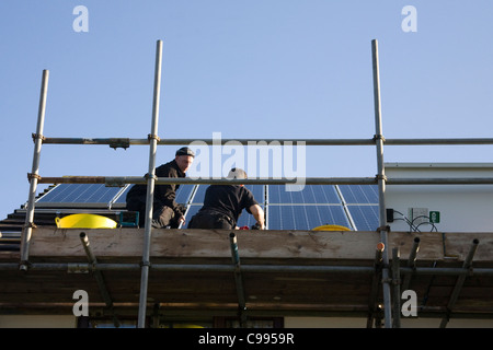 UK Two men standing on scaffolding fitting solar panels on a domestic house roof under Feed in Tariff FIT scheme - Stock Photo