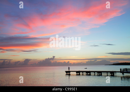 Curaçao Netherlands Antilles Dutch Piscadera Bay Caribbean Sea pier man standing rowboat coastline sunset twilight - Stock Photo