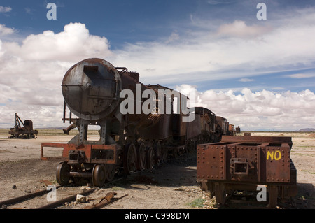 Dozens of old steam locomotives and tenders lie rusting in a desert 'train cemetery' a few miles outside Uyuni in - Stock Photo