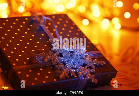 Red holiday background with present gift box & shiny blue snowflake, Christmas ornament and new year decoration - Stock Photo