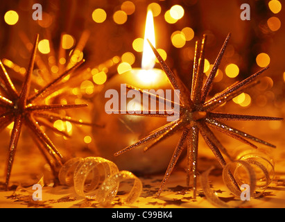 Golden holiday background with candle and Christmas tree ornament and decoration - Stock Photo