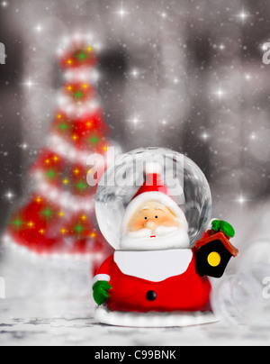 Snow globe Santa Claus, Christmas tree decoration, traditional winter holiday ornament with shiny blur lights background, - Stock Photo