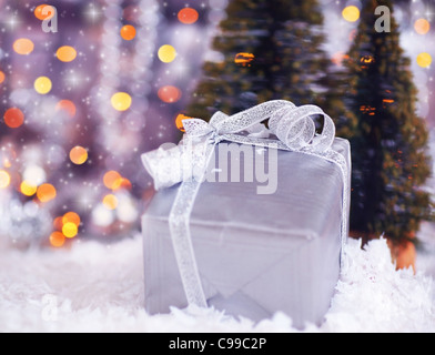 Winter holiday background with present gift box, silver ribbon ornament & Christmas snow decoration & defocus lights - Stock Photo