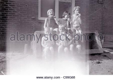 fading photo of children eating ice cream 1960s - Stock Photo