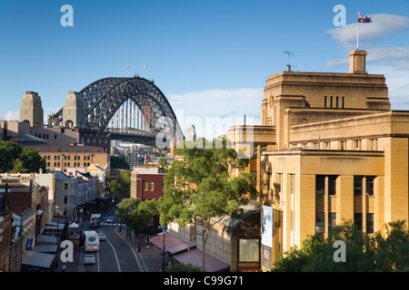View along historic George Street in The Rocks district, with Sydney Harbour Bridge beyond.  Sydney, New South Wales, - Stock Photo
