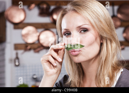 Italy, Tuscany, Magliano, Close up of young woman smelling basil leaf in kitchen, portrait - Stock Photo