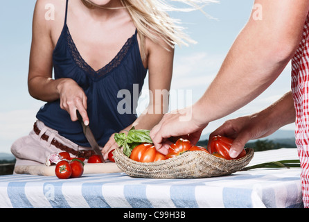 Italy, Tuscany, Magliano, Young man standing near table and woman cutting tomatoes, smiling - Stock Photo