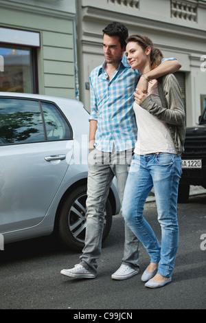 Germany, Berlin, Couple walking hand in hand through city street - Stock Photo