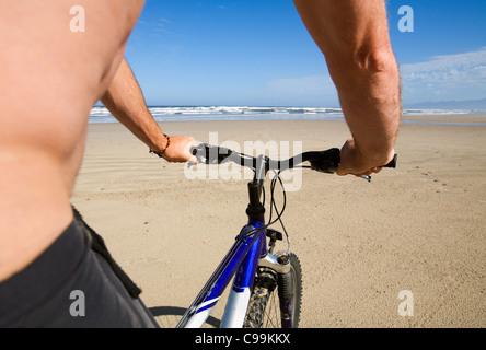 Man riding mountain bike on Ocean Beach. Strahan, Tasmania, Australia - Stock Photo