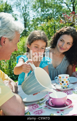 Germany, Bavaria, Family having coffee and cake in garden, smiling - Stock Photo