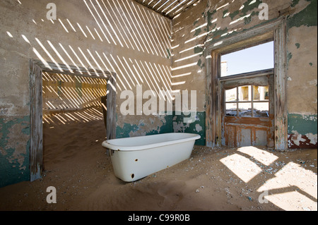 Bathtub in an abandoned house in Kolamanskop a former diamond mine in Namibia - Stock Photo