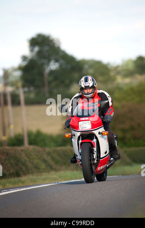 Motorcyclist riding along a rural road in England. - Stock Photo