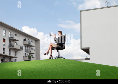 Germany, Bavaria, Munich, Businesswoman sitting on office chair and shouting through maghaphone - Stock Photo