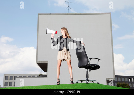 Germany, Bavaria, Munich, Businesswoman shouting through meghaphone in lawn - Stock Photo