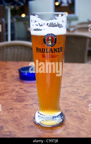 A printed glass of Paulaner weissbier wheat beer in a bar in Speyer, Rheinland-Pfalz, Germany pub table drinks glasses - Stock Photo