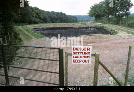 A settling lagoon for slurry to prevent pollution but securely fenced - Stock Photo
