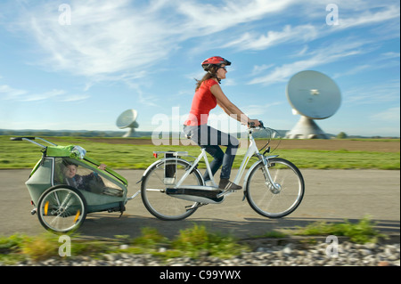 Germany, Bavaria, Raisting, Woman with girl riding child trailer near radio station - Stock Photo